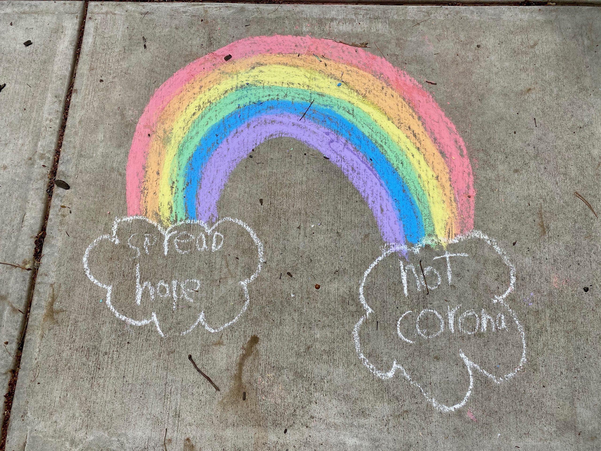 """Image of rainbow with clouds that read """"Spread Hope, Not Corona"""""""