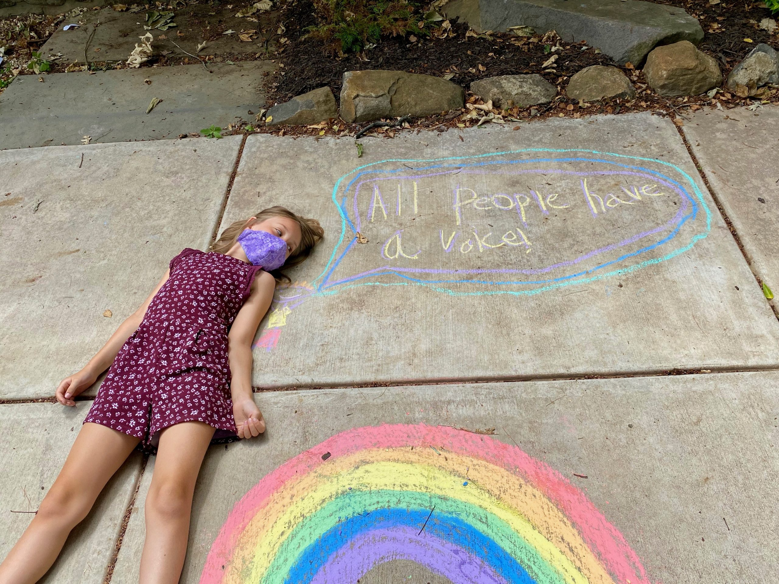 """Image of child lying on the ground next to speech bubble which says """"All People Have a Voice"""""""